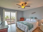 The master bedroom is equipped with a queen bed and direct access to the private deck.