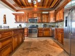 Fully stocked gourmet kitchen with stainless appliances, granite counters, and gorgeous hardwood!