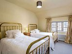 Bedroom 2, with two large single brass beds