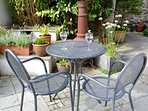 There is a small patio area with potted flowers in spring & summer, & seating for 4 people.