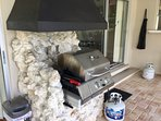 Built-in grill with chimney to vent smoke and extra propane tank