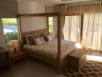 Master bedroom with king size four poster bed. The french doors open onto the patio.