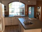 Kitchen centered around large island with picture window