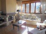 Salon avec cheminée insert fonctionnelle et TV écran plat