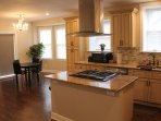 Stainless steel hood with full-range stove and granite countertops