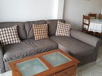 Large sofa bed and table containing a selection of books