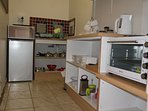Kitchen with stove, microwave, fridge/freezer, kettle, toaster, pots & pans, crockery, glasses etc