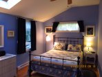 Summer blue bedroom with queen sized bed, large closet, skylight.