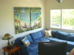 Living area with wide screen tv and local artist tropical artwork by Susanne Ball.