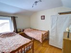 Twin bedroom with wooden floor and attractive coordinating furnishings