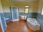 Bright bathroom with corner bath and separate shower cubicle