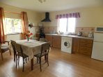 Large kitchen includes electric cooker, washing machine, tumble dryer, fridge freezer & microwave.