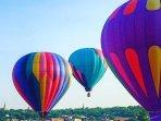 On a calm day balloons enjoy the river valley.