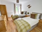 A charming twin bedroom with quality furniture and furnishings and view to the river