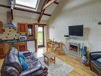 Open plan kitchen/living room with contemporary electric fire and Freeview TV