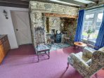 The sitting room has a woodburning stove in a stone inglenook fireplace