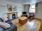 The living room features a log fire, Freeview TV and DVD player