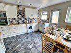 The kitchen/dining room has an electric ceramic hob and double oven, fridge/freezer, washing machine, dining table and...
