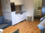 The kitchen includes a dishwasher, sink, hob, oven, microwave, kettle and toaster.