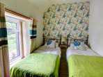 A twin room with bright co-ordinated decor and soft furnishings
