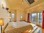 The master bedroom features a queen bed and a private balcony with views of the nearby ocean.