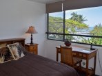 The makai (ocean side) bedroom features a queen bed and an ocean view.