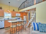 The modern, completely open kitchen boasts a gas-burning stove top, granite counters and a center island with bar...