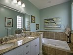 The elegant master bathroom is complete with a jacuzzi bathtub.