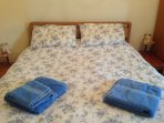 Kingsize bedroom with bedside tables chest of drawers and wardrobe.