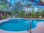 The heated pool and spa are screened and surrounded by lush tropical landscaping