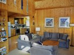 Open living room with a flat screen satellite TV/DVD player, Bluetooth speaker, glass front wood stove and spiral...