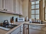 The small kitchen has everything you need for simple meals: fridge, cooktop, microwave, sink, and dishwasher