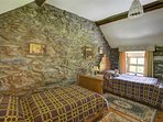 Interesting oak bedsteads and furnishings in the twin bedroom, with exposed stone walling