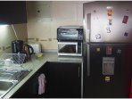 Full sized refrigerator, microwave, toaster oven, toaster, coffee pot & hot water pot.