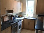 Kitchen with washing machine, gas hob electric oven, microwave