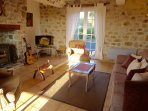 Cosy cottage living room with seating for 6 and a wood burning stove. Flat screen TV w/ UK channels