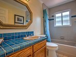 Get ready for your day at the beach in this full bathroom.