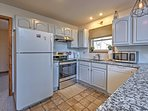 The fully equipped kitchen includes granite countertops and a breakfast bar with seating for 3.