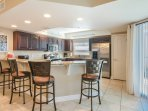 Spacious kitchen with large bar and seating for 4.