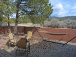 The east facing adobe wall enclosed patio with hammock, lounge chairs, shade tree & Taos mountain views....