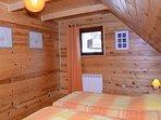Chambre avec deux lits simples donnant côté jardin commun et route.