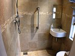 Travertine tiled wet room with shower,wc and whb.