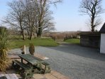 Grounds surround the property with lawn, patio area with garden furniture.