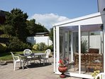 Sunny conservatory with double doors leading to rear patio and garden