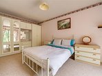Large double bedroom with patio doors leading to rear enclosed garden