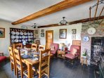 The large dining room with beautiful slate floor has an Aga and a feature bread oven in the brick fireplace