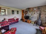 Classic leather Chesterfield sofas and armchairs furnish the sitting room, which also has an interesting exposed stone...