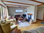 The lovely beamed sitting room, with oak floor, has a woodburning stove in the beamed fireplace
