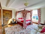 The master bedroom boasts a stylish four-poster bed and a sofa