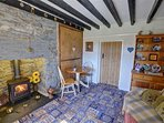 The beamed living room has a pine dresser and table and chairs by the woodburner
